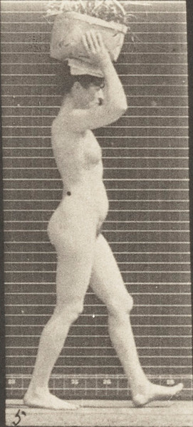 Nude woman walking and carrying basket on head