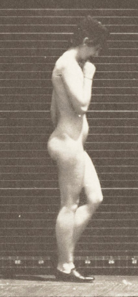 Nude woman walking with shoes on and right hand at chin