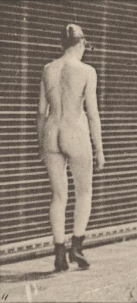 Nude woman walking in high-heeled boots