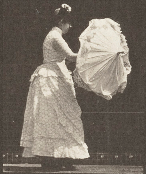 Woman walking and opening a parasol