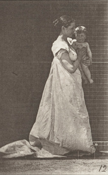 Draped woman walking and carrying child on her left arm