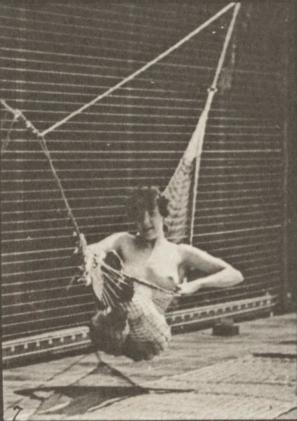 Nude woman getting into a hammock