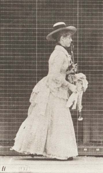 Woman in long dress with a parasol in left hand stooping and lifting a handkerchief