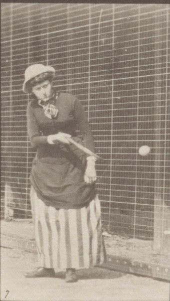 Woman in long dress playing lawn tennis