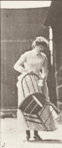 Draped woman stepping on a chair and reaching up
