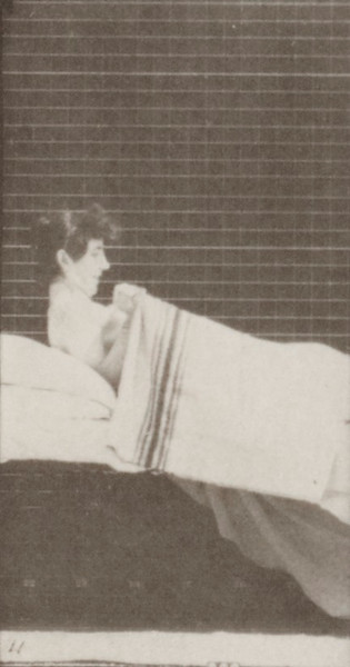 Nude woman getting into bed