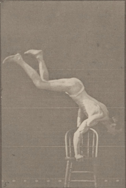 Man in pelvis cloth performing handstand on chair