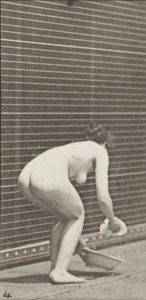 Nude woman stooping, lifting a basin, wiping it and turning