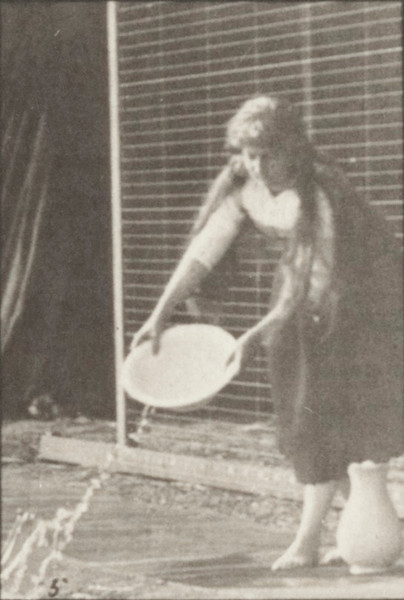 Woman in long dress lifting and emptying a basin of water and turning