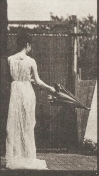Draped woman opening a parasol and turning around