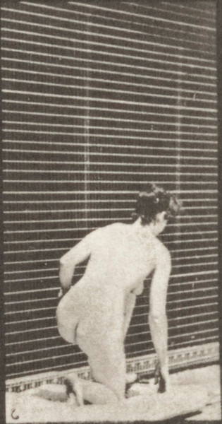 Nude woman arising from kneeling and turning