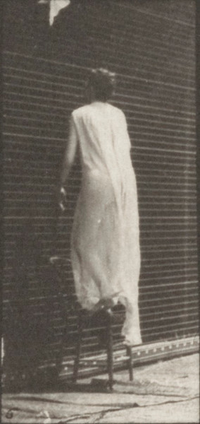 Draped woman stepping on a chair, reaching up and descending