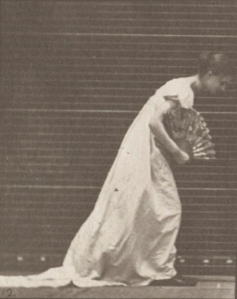 Woman in long dress curtseying, a fan in right hand