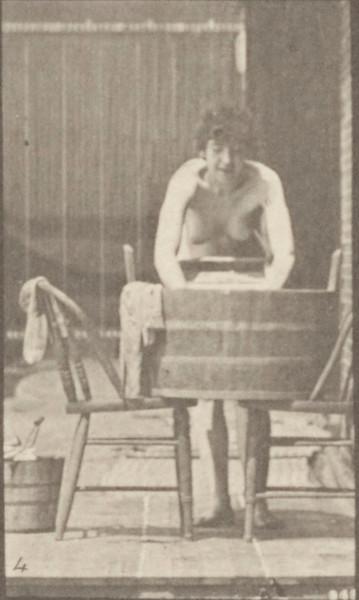 Nude woman washing clothes at a tub