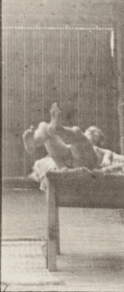 Nude man lying on a couch and turning over on side