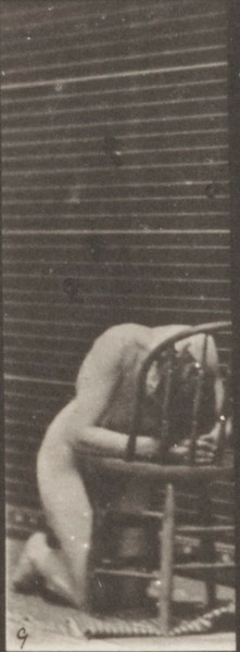 Nude woman kneeling, elbows on chair and hands clasped