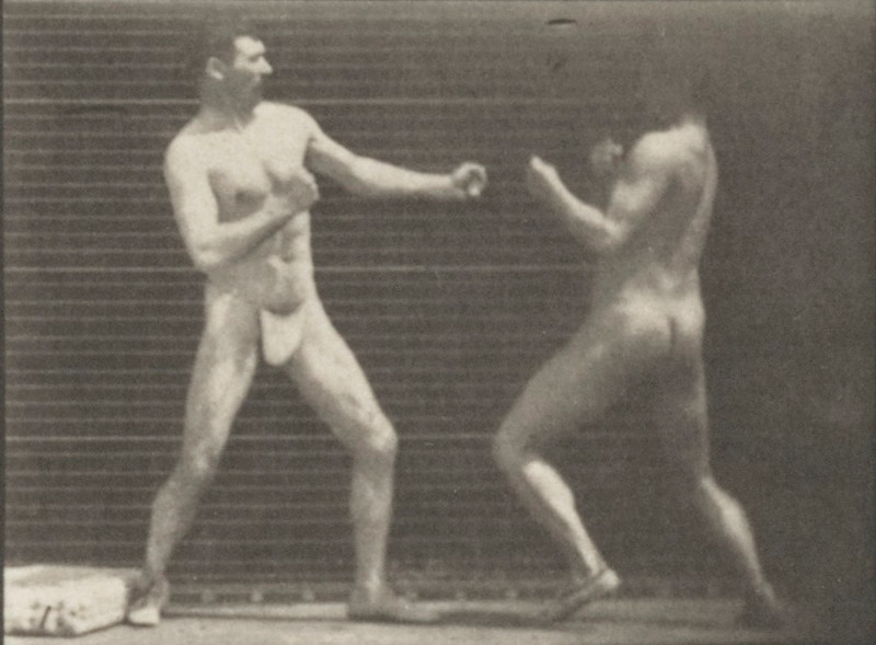 Two men in thong underwear boxing, one man knocking the other one down