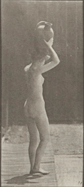 Nude woman stooping, lifting a water jar to head and turning