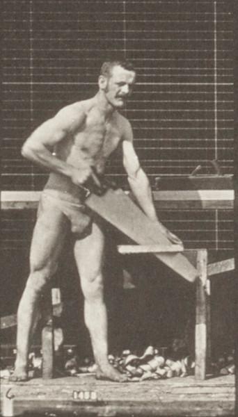 Man in pelvis cloth sawing a board