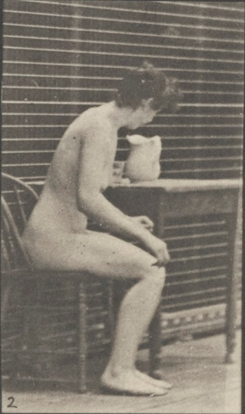 Nude woman sitting crossing legs and filing a goblet from a pitcher