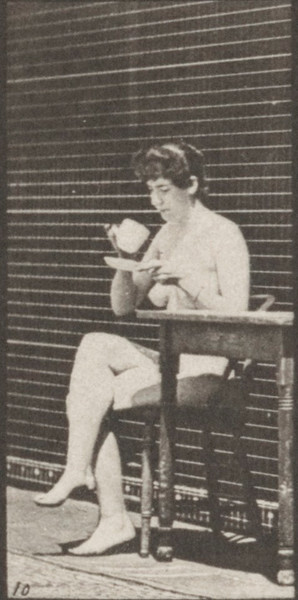 Nude woman sitting on a chair, crossing legs and drinking from a teacup