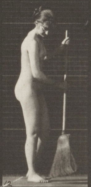 Nude woman stooping, lifting a broom and sweeping