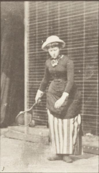 Woman in long dress playing lawn tennis