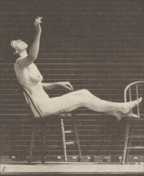 Nude woman sitting down and placing feet on chair