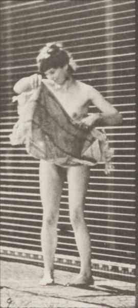 Nude woman lifting a cloth from the ground, placing around shoulder and turning