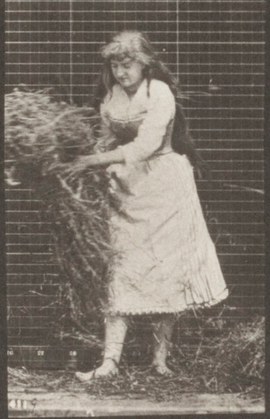 Draped woman lifting handfuls of hay, turning and throwing it down
