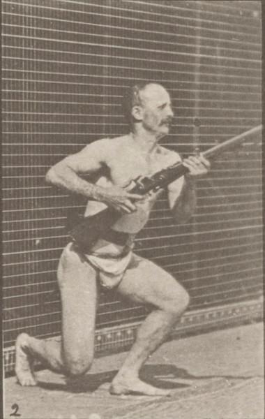 Man in pelvis cloth kneeling, firing a bayonet and rising