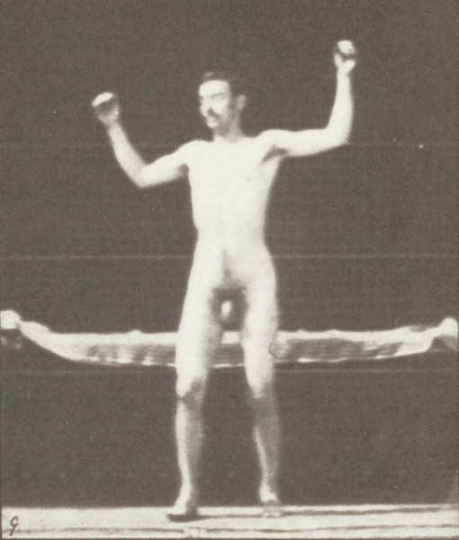 Nude man arising from couch and stretching arms