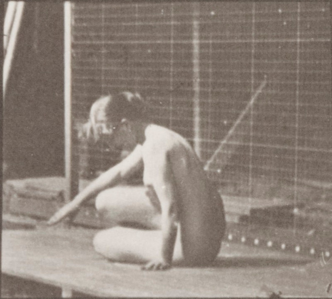 Nude woman turning and changing position while on the ground