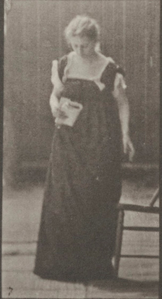 Woman in long dress placing a chair, sitting and reading