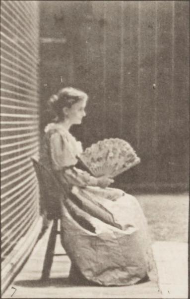 Woman in long dress sitting and flirting a fan