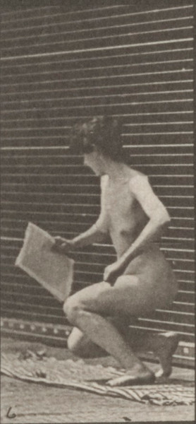 Nude woman lying on the ground and reading
