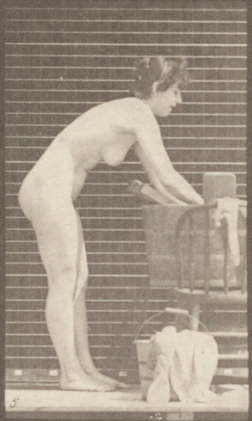 Nude woman washing clothes at a tub