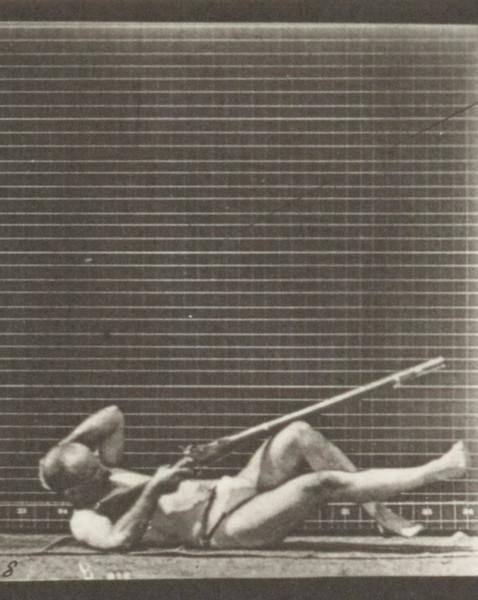 Man in pelvis cloth lying on back and firing bayonet