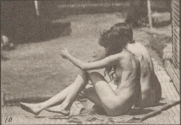 Two nude women turning around and sitting on the ground