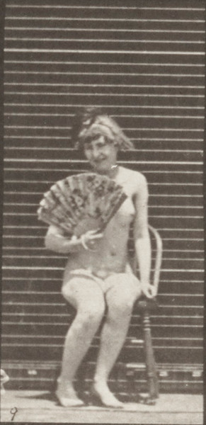 Nude woman sitting down on a chair and opening a fan