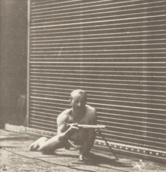 Man in pelvis cloth lying prone and firing a bayonet