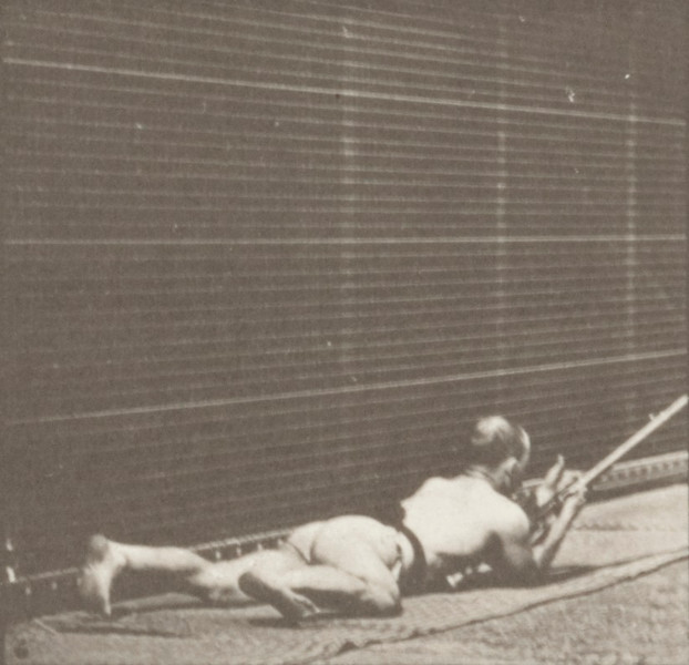 Man in pelvis cloth lying prone and firing a bayonet