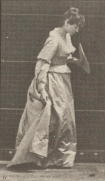 Woman in long dress stooping and lifting dress with a fan in left hand