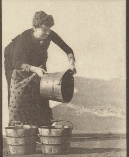 Draped woman emptying a bucket of water