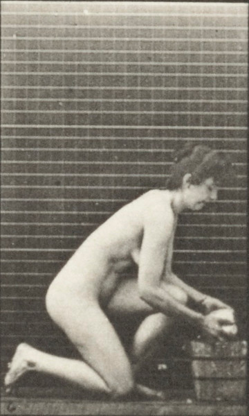 Nude woman kneeling on right knee and scrubbing the floor