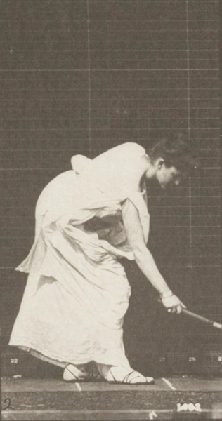 Woman in long dress playing with a tennis racket and ball
