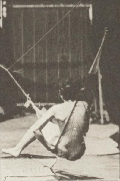 Nude woman getting into a hammock