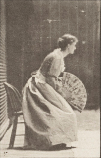 Woman in long dress sitting and flirting a fan