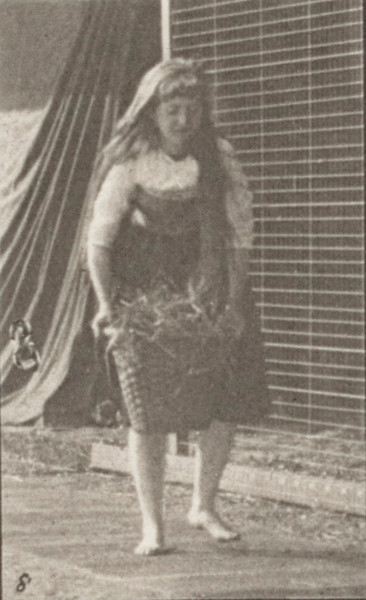 Woman in long dress stooping, lifting and carrying a 30-lb basket