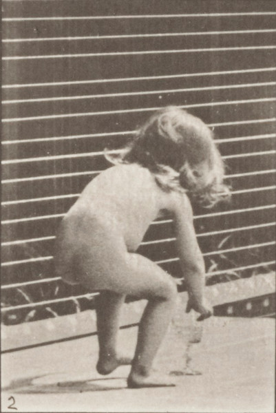 Nude child stooping and drinking